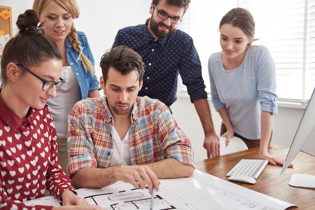 Collega's op kantoor met architectuurplannen en een computer