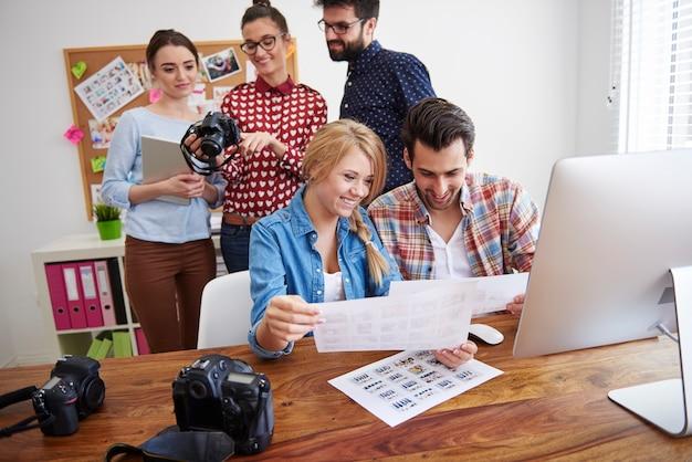 Collega's op kantoor met fotocamera's en een computer Gratis Foto