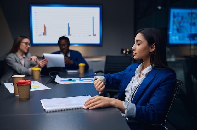 Collega's over zakelijke onderhandelingen in nachtkantoor. slaperige mannelijke en vrouwelijke managers, donker zakencentruminterieur, moderne werkplek