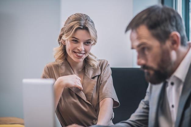 Collega's, relaties. geïnteresseerde lachende vrouw met blond golvend haar en ernstige bebaarde zakenman aan het werk op laptop