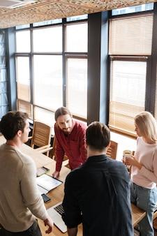 Collega's staan tijdens het werk met laptops en notebook.