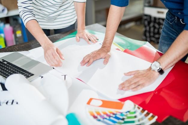 Collega's van drukkerij die papier aanraken