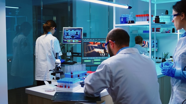 Collega's van wetenschappers die 's nachts in een chemisch modern uitgerust laboratorium werken en testresultaten analyseren