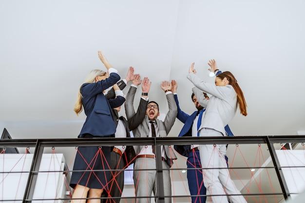 Collega's verbinden zich op hun werkplek en juichen voor teamgeest.