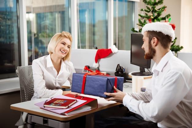 Collega's vieren kerstfeest in office glimlachend geven presenteert.