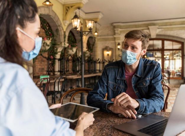 Collega's werken binnenshuis samen terwijl ze medische maskers dragen