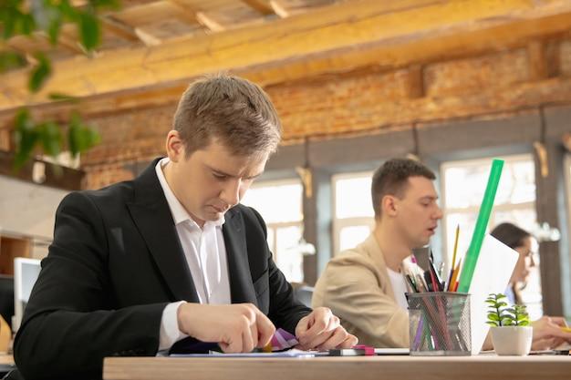 Collega's werken samen in een kantoor met behulp van moderne apparaten tijdens creatieve vergaderingen. briefpapier, laptop, documenten. concept van zaken, kantoor, financiën, open ruimte.