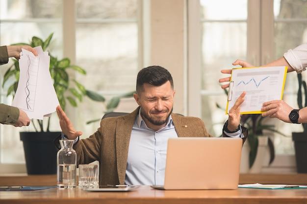Collega's werken samen in een modern kantoor met behulp van apparaten en gadgets tijdens creatieve vergaderingen