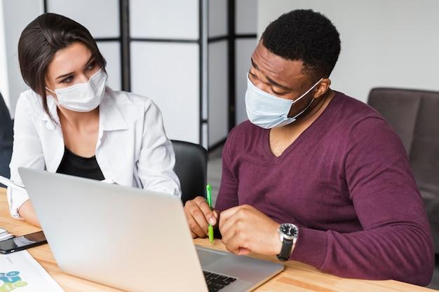 Collega's werken samen tijdens pandemie op kantoor met maskers op