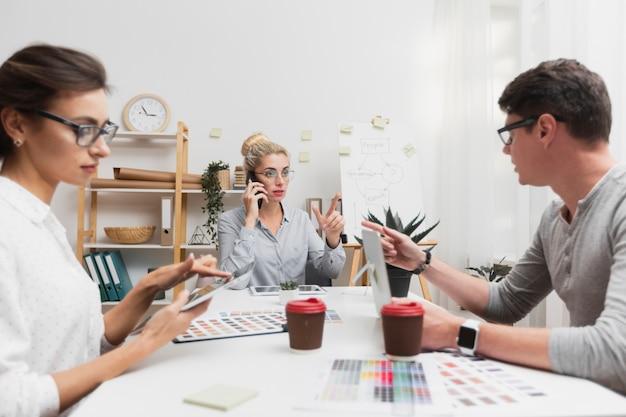 Collega's zitten aan een tafel en praten over zaken