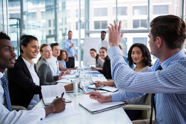 Collega steekt zijn hand op tijdens de vergadering