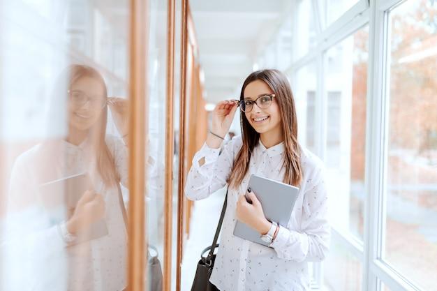 College meisje permanent naast prikbord met tablet in arm en tas op de schouder