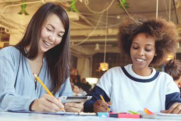 College meisjes doen thuisopdracht in cafetaria met behulp van digitale tablet en notities maken op papier.