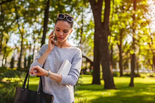 College student praten op mobiele telefoon in park