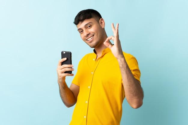 Colombiaanse man met behulp van mobiele telefoon weergegeven: ok teken met vingers