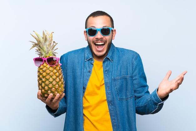 Colombiaanse man met een ananas met zonnebril met verrassing en geschokte gelaatsuitdrukking