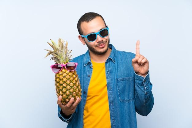 Colombiaanse man met een ananas met zonnebril tellen nummer één teken