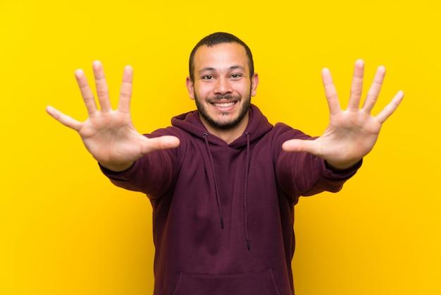 Colombiaanse man met sweater op gele muur die tien met vingers telt