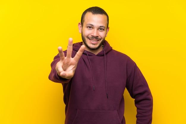 Colombiaanse man met sweatshirt over gele muur gelukkig en drie met vingers tellen