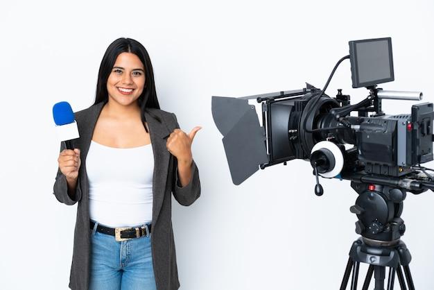Colombiaanse verslaggeefster die een microfoon houdt en nieuws over wit met duimen op gebaar en het glimlachen rapporteert