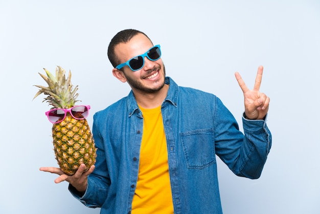 Columbiaanse mens die een ananas met zonnebril houdt die en overwinningsteken glimlacht toont