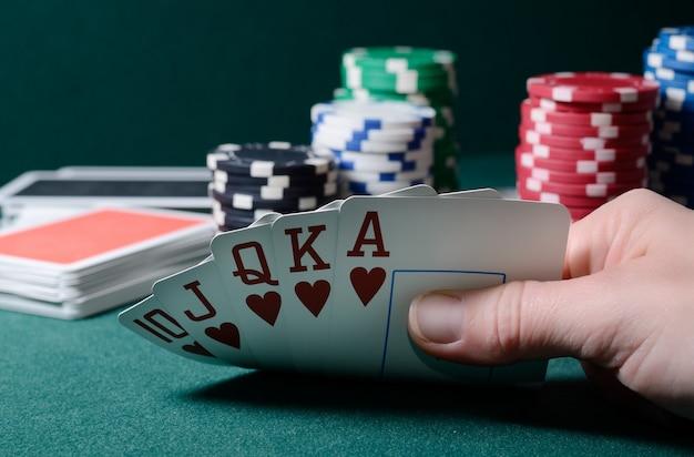Combinatie van casinofiches en royal flush kaarten op de groene tafel. pokerspel thema