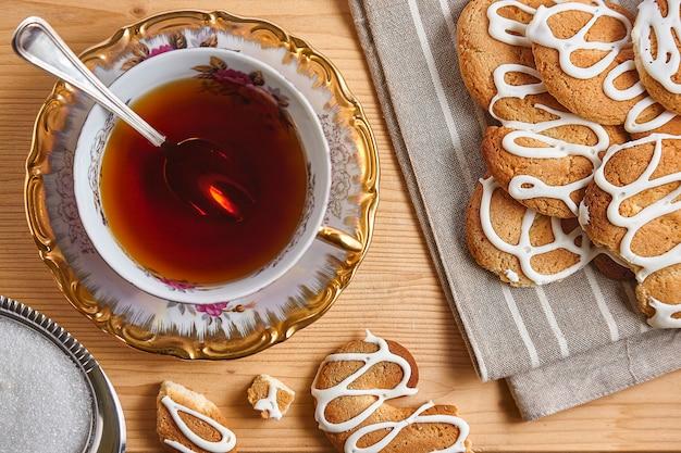 Combinatie van eten met thee en koekjes op een houten tafel van bovenaf