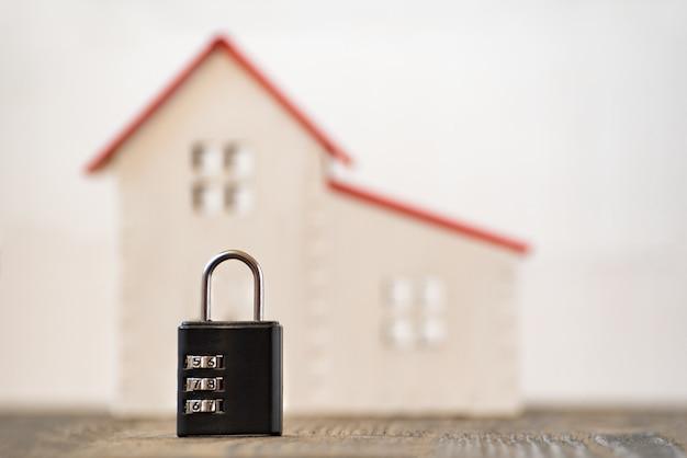 Combinatieslot en modelwoning op vage achtergrond. huis en veiligheidsconcept.