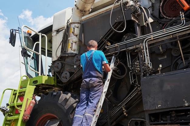 Combineer machineservice, monteur die motor buitenshuis repareert.