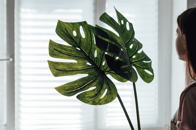 Comfort in huis creëren. vrouw met een vaas en kunstmatige bladeren ter decoratie. verbetering van het huis, kamers.