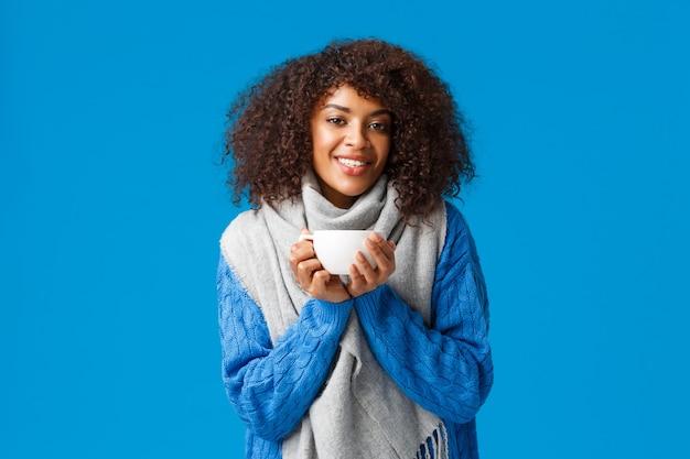 Comfort, tederheid en warmte concept. charmante mooie afro-amerikaanse vrouw met afro kapsel, in trui en sjaal, opwarmen met lekker kopje thee, genieten van warme koffie.