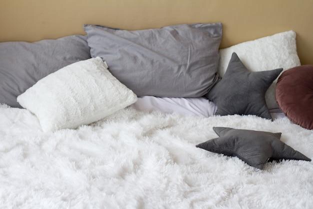 Comfortabel bed met kussens in lichte slaapkamer, home comfort concept, kopie ruimte