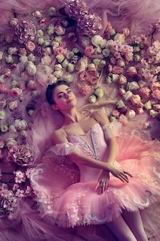 Comfortabel. bovenaanzicht van mooie jonge vrouw in roze ballet tutu omgeven door bloemen. lentestemming en tederheid in koraallicht.