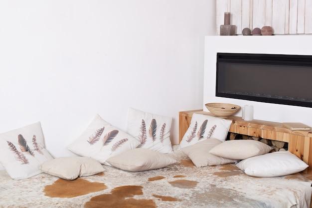 Comfortabel huis. scandinavisch interieur met kussens. moderne landhuis interieur met houten bed, brandhout, open haard. interieur van een moderne houten slaapkamer in landelijke stijl (rustiek). warmte in huis