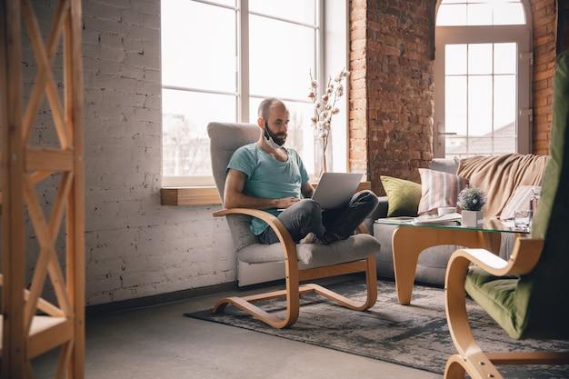 Comfortabel. jonge man thuis terwijl hij in quarantaine zit en freelance online werkt.