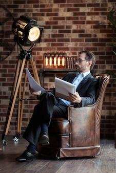 Comfortabel voelen. aardige aangename knappe man met bril en zijn benen gekruist zittend in de fauteuil