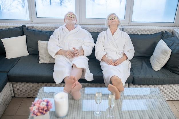 Comfortabel voelen. ouder paar in witte gewaden ontspannen in een kuuroord en comfortabel voelen