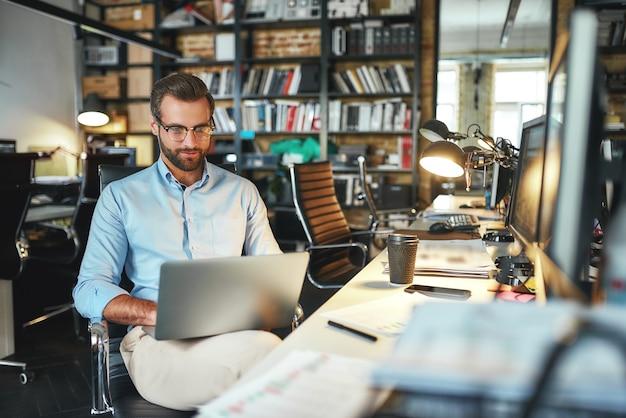 Comfortabel werkplekportret van een jonge en succesvolle bebaarde man in een bril die met een laptop werkt