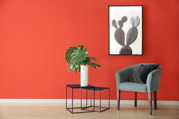Comfortabele fauteuil en tropische bladeren op tafel in de buurt van kleur muur in kamer