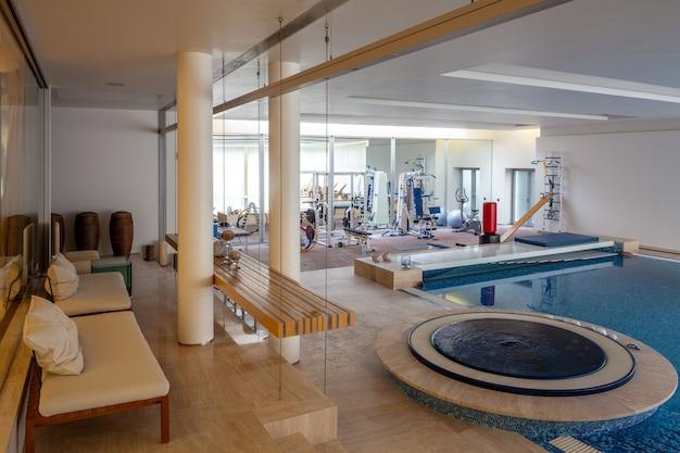 Comfortabele fitnessruimte in privéhotel met zwembad met trainingsapparatuur en banken voor ontspanning