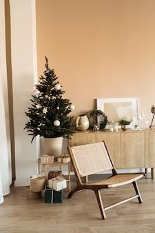 Comfortabele gezellige woonkamer versierd met kerstboom met cadeautjes, rotan stoel.