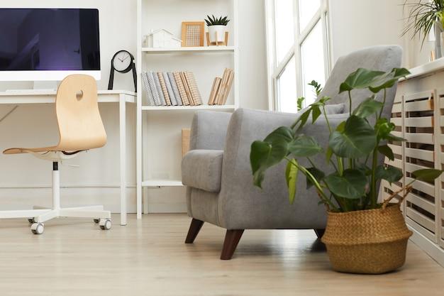 Comfortabele grijze fauteuil in een knus hoekje van een modern scandinavisch huis versierd met planten