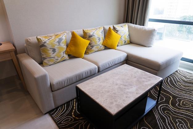 Comfortabele hoekbank met ouderwetse kussens en een salontafel op tapijt in de woonkamer