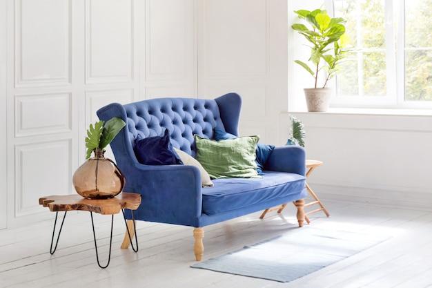 Comfortabele klassieke blauwe bank met kussens en houten salontafel in eenvoudig wit appartement