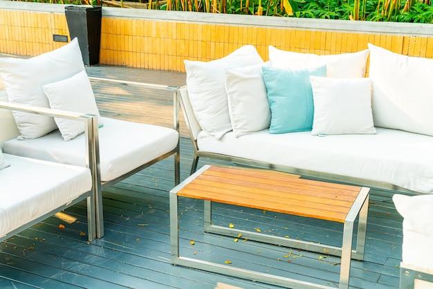 Comfortabele kussens op terrasstoel en tafel
