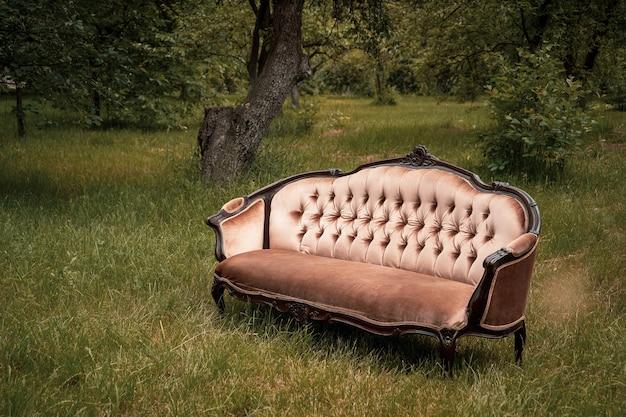 Comfortabele luxe bank midden in een groene tuin op een zomerse dag. huismeubilair in de achtertuin in de natuur. kopieer ruimte.