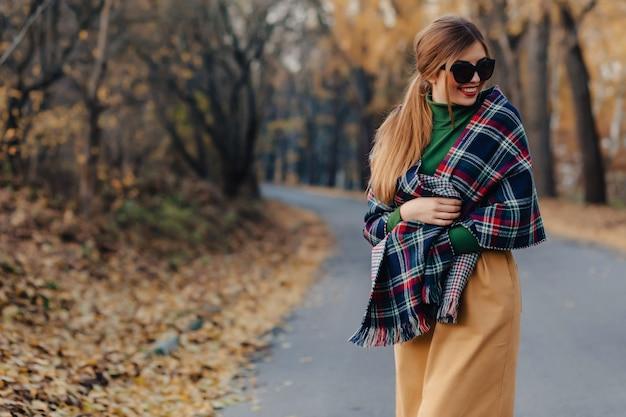Comfortabele modieuze jonge meisjesgang bij de herfst kleurrijk park