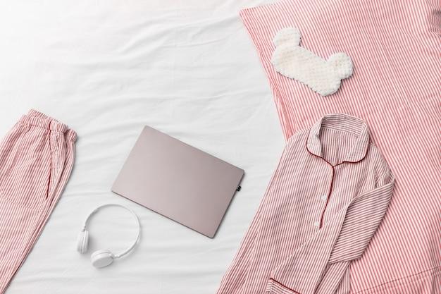 Comfortabele roze pyjama, koptelefoon, kussen, donzig slaapoogmasker. werken vanuit huis.