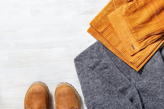 Comfortabele warme outfit voor koud weer. heldere corduroy broek gebreide grijze pullover en comfortabele schoenen. vrouw accessoires. bovenaanzicht. plat liggen.