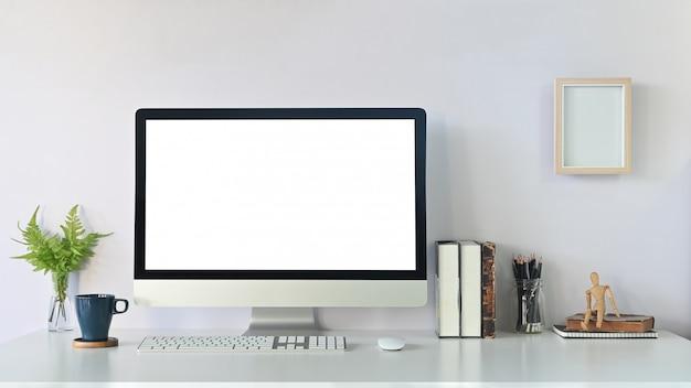 Comfortabele werkplek computer mockup, koffie, boeken, potlood en plant met fotolijst op wit bureau.